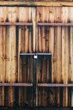 Wooden gates in a barn. With a lock and rusty loops stock image