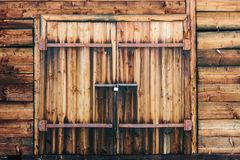 Wooden gates in a barn. With a lock and rusty loops stock photo