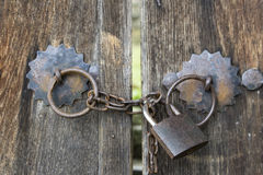 The wooden gates locked on an iron padlock with chain in bulgarian village Stock Image