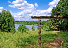 Wooden gates and walkway near lake Svetloyar. Wooden gates and footpath against green forest, lake Svetloyar and blue sky Royalty Free Stock Photo