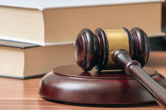 Wooden gavel and books in background. Law and justice concept Stock Photos