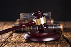 Wooden gavel and books on wooden table Stock Photos