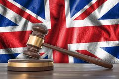Wooden gavel and flag of UK on background - law concept. Wooden gavel and flag of United Kingdom on background - law concept. 3D rendered illustration Royalty Free Stock Photos