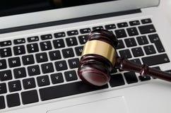 Wooden gavel on laptop keyboard Stock Photo
