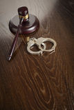 Wooden Gavel and Pair of Handcuffs on Table Stock Photography