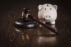 Wooden Gavel and Piggy Bank on Table Royalty Free Stock Photos
