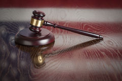 Wooden Gavel Resting on Flag Reflecting Table Stock Image