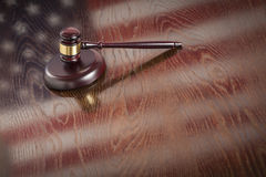 Wooden Gavel Resting on Flag Reflecting Table Stock Photo