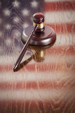 Wooden Gavel Resting on Flag Reflecting Table Royalty Free Stock Image