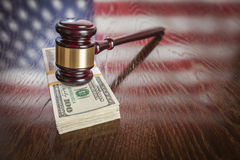 Wooden Gavel Resting on Money with American Flag Reflection Stock Photo