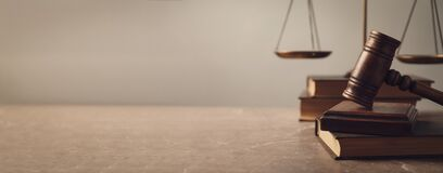 Wooden gavel with scales of justice and books on lawyer`s table. Banner design