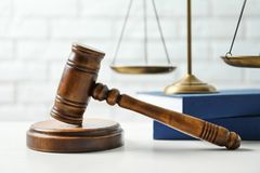 Wooden gavel, scales of justice and books on table against brick wall, closeup. Law. Concept stock image