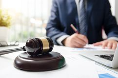 Wooden gavel on table. Attorney working in courtroom. Stock Image