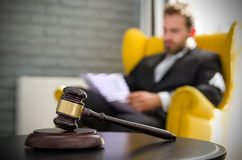 Wooden gavel, working lawyer in background. Attorney business judgment justice suite analyzing authority background concept Royalty Free Stock Images