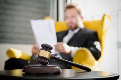 Wooden gavel, working lawyer in background Royalty Free Stock Photos