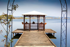 Wooden gazebo on dock over peaceful lake Stock Photo