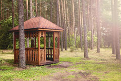 A wooden gazebo in the forest. A wooden Arbor in a pine forest. Place for leisure travelers. Concept: environment, protect nature, do not leave the garbage in Stock Image