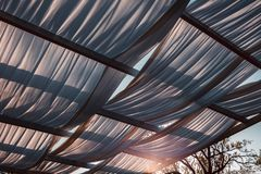 Wooden gazebo in the golden hour light, almost sunset: close up of white cloths, soft light, summer mood, vacation, holiday and royalty free stock photos