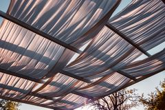 Wooden gazebo in the golden hour light, almost sunset: close up of white cloths, soft light, summer mood, vacation, holiday and royalty free stock photography