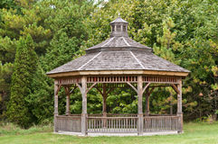 Wooden Gazebo in a Park. A wooden gazebo stands in front of some green trees in a park Royalty Free Stock Photography