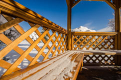 A wooden gazebo in a park in the snow and blue sky Royalty Free Stock Image