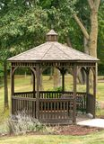Wooden gazebo in park. Surrounded by trees Royalty Free Stock Image