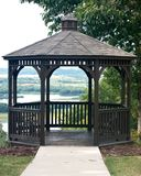 Wooden gazebo in park. Surrounded by trees Stock Image