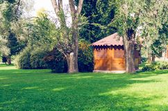 Wooden gazebo in park surrounded by trees.  Royalty Free Stock Photography