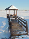 Wooden gazebo by the pond at winter. Wooden gazebo and planked footway by the covered by ice river on a clear sunny winter day in a sanatorium on the outskirts Stock Photos
