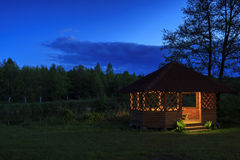 Wooden gazebo on the river bank. At night Stock Photo