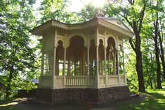 Spa arbor. Wooden gazebo at the spa in Jeseník. The arbor is white, carved, surrounded by trees stock photography