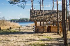 Wooden gazebo under reed roof with table in middle stand on shore of forest lake with sandy beach surrounded by pine trees against Royalty Free Stock Photography