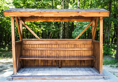 A wooden gazebo in the woods. Wooden gazebo with a bench in the forest Royalty Free Stock Images