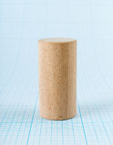 Wooden geometric shape cylinder. On graph paper Stock Image