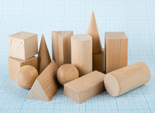 Wooden geometric shapes. On graph paper royalty free stock photography