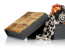 Wooden Gift Box with Jewelry. Small Black wooden box with light wood tiles on top. Box is open with ethnic jewelry spilling out royalty free stock images
