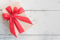 Wooden gift box with red ribbon bow on vintage background Royalty Free Stock Images