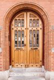 Wooden and glass door. Closed antique wooden and glass door in red brick building Royalty Free Stock Photography