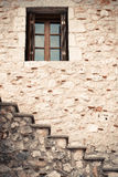 Wooden and glass window in a stone wall with stairs. Small wooden and glass window in a stone wall with stairs Stock Image