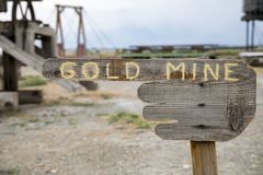 Gold Mine Sign. A wooden gold mine sign on a pointing hand Royalty Free Stock Images