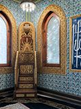 Wooden golden ornate minbar Platform,  wooden arched window framed by golden ornate floral pattern, and ceramic tiles wall with Stock Images