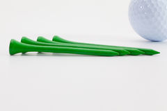 Wooden golf tees and golf ball on the white table Royalty Free Stock Images