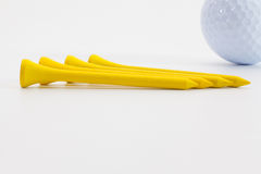Wooden golf tees and golf ball on the white table. Yellow wooden golf tees and golf ball on the white table Stock Photo