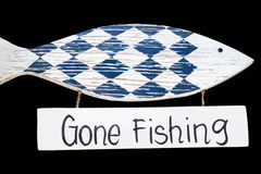 Wooden gone fishing sign. Isolated on black background royalty free stock photo