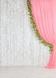 Wooden gray wall with a pink curtain and flowers. Stock Photography