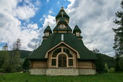 Wooden green chapel on a hill in the forest. Rustic chapel. Church against the forest and sky. Orthodox, christian monastery in su. Mmer royalty free stock image