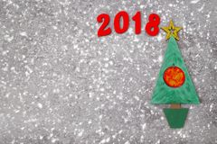 Wooden Green Christmas tree and sign 2018 from wooden redletters, gray concrete background. Happy new year 2018 backdrop. Greeting card Royalty Free Stock Photography