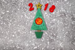 Wooden Green Christmas tree and sign 2018 from wooden redletters, gray concrete background. Happy new year 2018 backdrop. Greeting card Royalty Free Stock Images