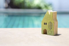 Wooden green miniature house over swimming pool background Stock Photos