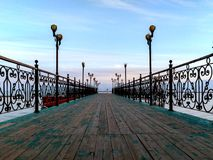 Wooden green pier on lake Issyk-kyl stock photo